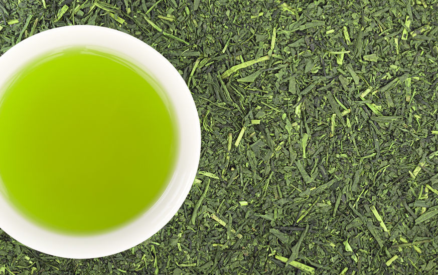 Cup of green tea with green tea leaves