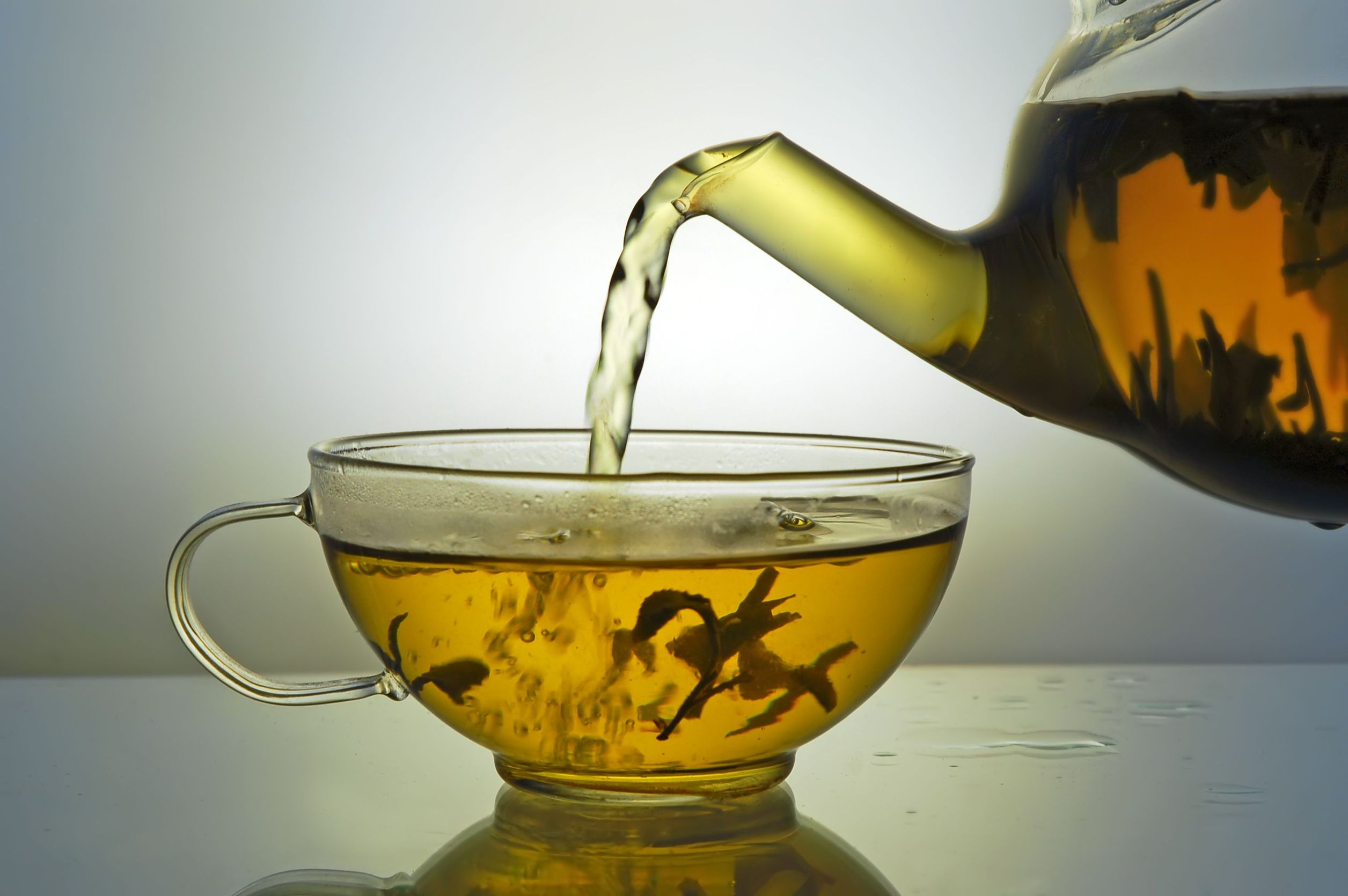 3007241 - green tea pouring into glass cup from teapot on blue background