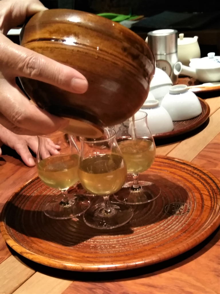 pouring sencha green tea in glass teacups
