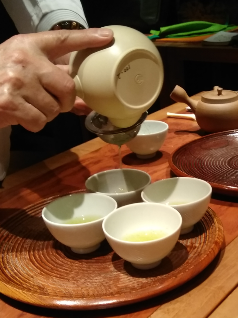 Pouring sencha green tea from kyusu into small tea cups